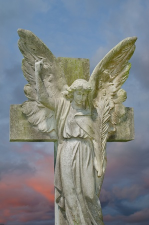 angel headstone: Pre 1900 stone statue gravestone of angel with large wings against a colourful sky.