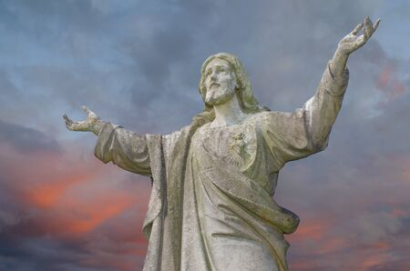 death and dying: Pre 1900 worn stone statue of Jesus on a gravestone with arms outstretched against fiery cloudy sky. Stock Photo