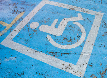 quite: Handicapped parking sign on the road is quite old. Stock Photo