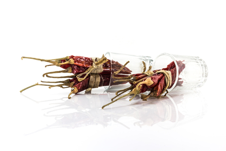 spicey: Red chillies in a glass on a white background.