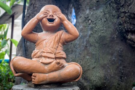 chinese symbol: Clear statue of a smiling child under the big tree.