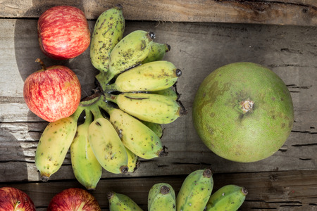 put together: Many fruits put together on the floor and wooden background.