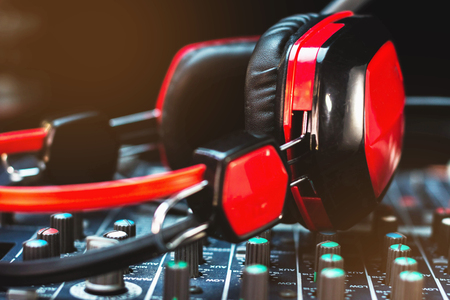 audio mixer: Closeup red headphones and audio mixer on a black background. Low-key photo.