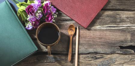 Bovenaanzicht zwarte koffiemok met notitieboekje en bloem. Stockfoto