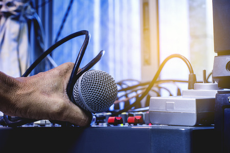 Mans hands control the sound. The microphone and the audio mixer. Stock Photo