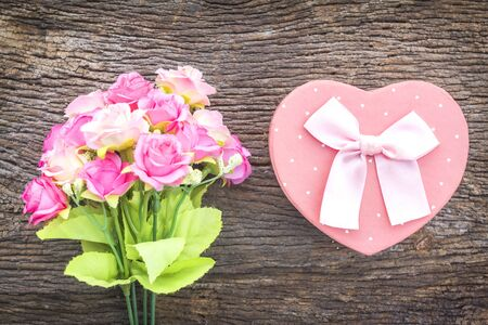 Heart shape gift box with artificial flowers on wooden background.