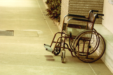 Very old wheelchair for patients left alone in the hospital. Stock Photo