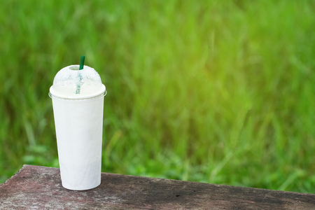 Coffee cup white paper background of green grass on a cement bench.