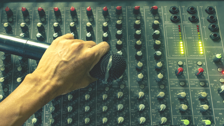 Hand of Sound Engineering holding a wireless microphone on the audio collection. Stock Photo