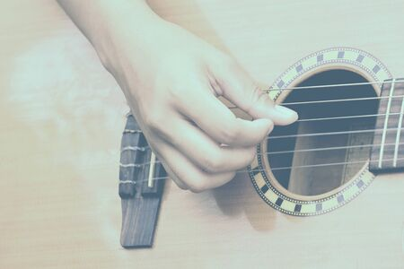 The hand of the girl is playing a guitar like picking.
