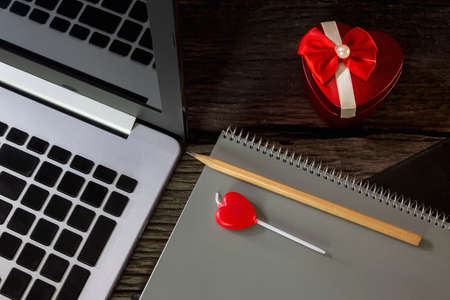 A red heart shaped box and a heart shaped candle and a brown pencil on a memory journal. The concept of love day. 免版税图像