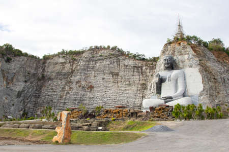 A large Buddha image carved from a rocky mountain. Buddhist history study garden.