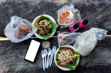 White Mockup Mobile phone tableware. Papaya salad, fried chicken, sweet liver, glutinous rice, juice. And digital communication tools on an old wooden table. 免版税图像
