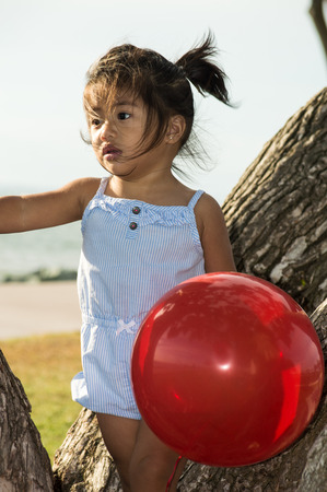 A young girlstanding on a tree with a balloon photo