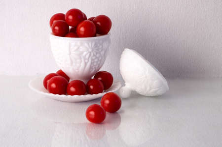 bowel: A bowel made of milk glass overflowing with cherry tomatos Stock Photo