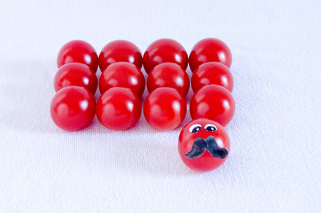 lumpy: Cherry tomatoes in formation with one in command Stock Photo