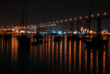 forground: Coronado bridge at night withreflections and silhouettedsail boats in the forground