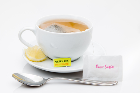Green tea in a cup with lemon a teaspoon. Stock fotó