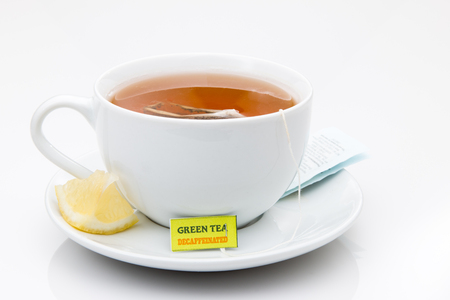 Green Tea in a white cup with lemon on a saucer.