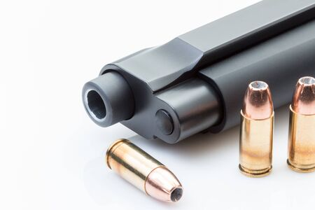 Barrel of a handgun with bullets on a white background.