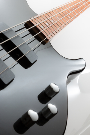Electric bass guitar with chrome knobs in vertical.