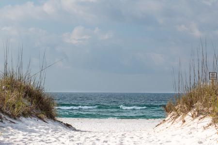 Pathway through the sand dunes on a white sandy beach.