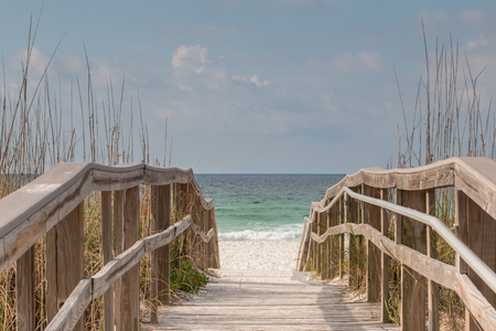 Wooden boardwalk leading to a white sandy beach. Stock Photo