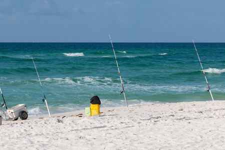 Fishing rods in the sand at the shore of a sandy beach.