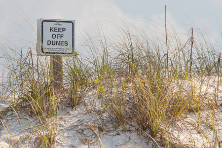 Keep off Dunes sign on a sand dune at the beach.