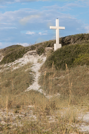 White cross on a sand dune at the beach. Imagens