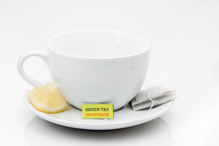 Green Tea bag on a saucer with a cup and lemon wedge.