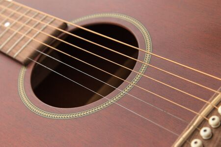Acoustic guitar close up with strings and mahogany wood.