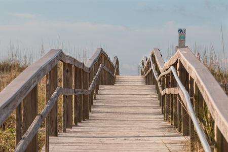 Boardwalk through the dunes to the beach. Stock Photo