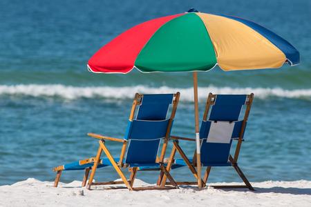 Beach umbrella and empty chairs on a white beach. Stock Photo