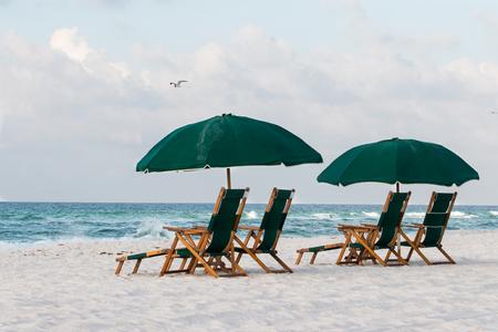 Beach umbrella and chairs on a white sandy beach. Stock Photo