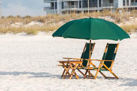 Beach umbrella and chairs on a white beach. Stock Photo