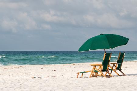 Beach umbrella and chairs on a white sand beach. Stock Photo