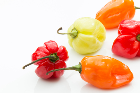 Habanero peppers in assorted colors on white background. Banco de Imagens
