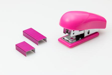 engrapadora: Pink stapler and staples mini size on white background.