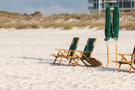 Beach chairs and umbrella on a white sand beach.