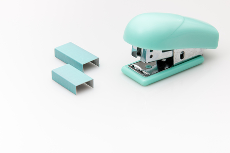office stapler: Green stapler and staples on a white background. Stock Photo