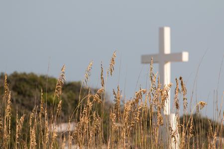 White cross on a sand dune. Stock Photo