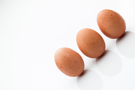 Three brown eggs on a white background.