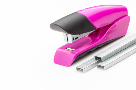 office stapler: Pink stapler and staples on a white background. Stock Photo