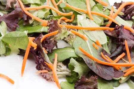 Salad greens with carrots on white.