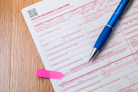 Medical claim form with pen and post it note.