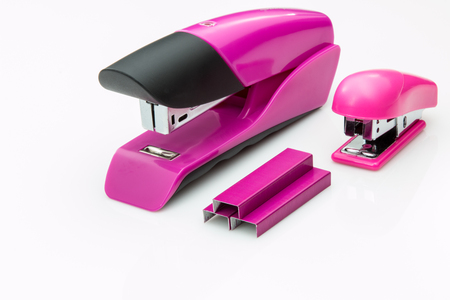 Two pink staplers and staples on white background.