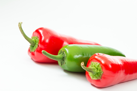 Red chili peppers and green jalapeno pepper on white background.
