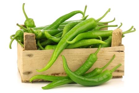 pimientos: Recién cosechadas chiles jalapeños en una caja de madera sobre un fondo blanco