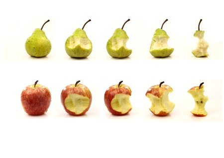 A fresh apple and a fresh pear in different stages of being eaten on a white background Banque d'images